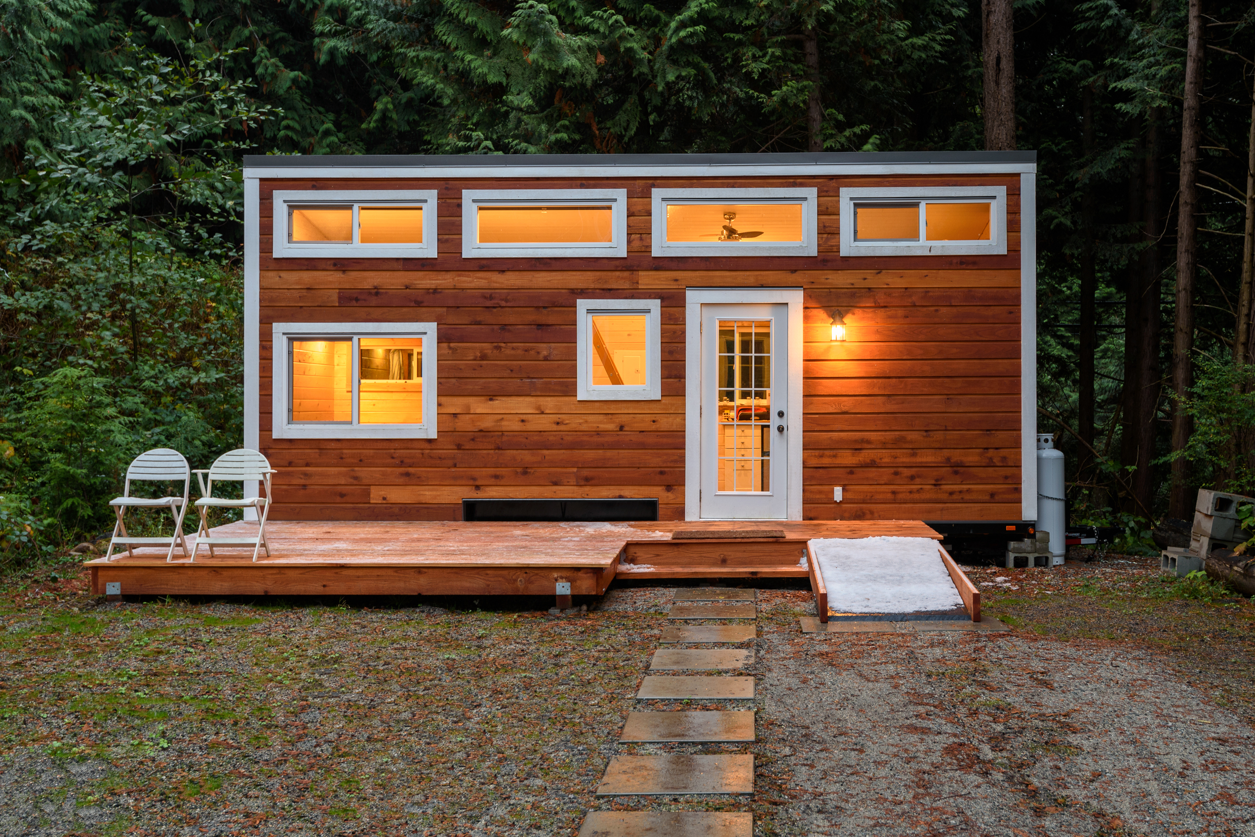 Small,Wooden,Cabin,House,In,The,Evening.,Exterior,Design.