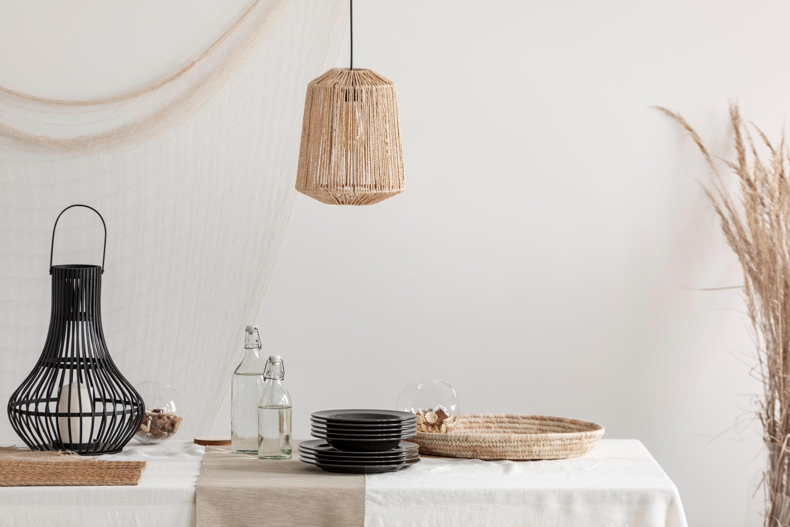 Rattan,Lamp,Above,Dining,Table,With,Wicker,Plateau,And,Black